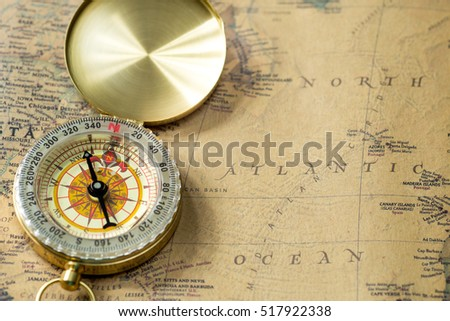 Illustrative editorial, Nizhny Novgorod, Russia - October 5, 2016. old gold compass with cover on vintage map, macro background