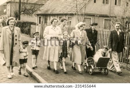 ILOWA, POLAND, CIRCA FIFTIES: Vintage photo of family with children walking down the street - stock photo