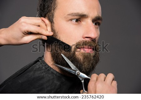 Image as somebody is trimming the beard of a young man on the grey background. - stock photo