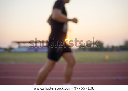 image blur of a man run at the running track on soccer stadium, at sunset - stock photo