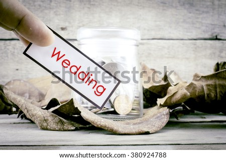 image concept cropped finger holding white card with black frame with word WEDDING. background with coin in glass jar surrounded by dry leaves and wood. - stock photo