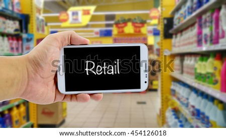 image concept, cropped hand holding smartphone with word RETAIL over blurred hypermarket background - stock photo
