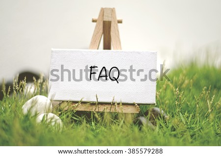 image concept white frame canvas on wooden tripod with word FAQ. Blurred and soft focus background with green grass and white stone - stock photo