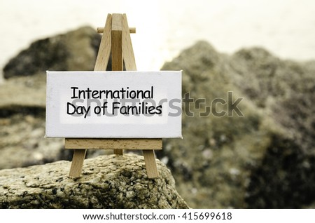 Image concept with word INTERNATIONAL DAY OF FAMILIES on white canvas and easel. blurred rock image background at the shore during sunset.