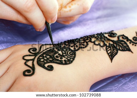 Image detail of henna being applied to hand - stock photo