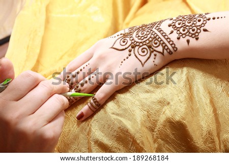 Image detail of henna being applied to hand over golden fabric - stock photo