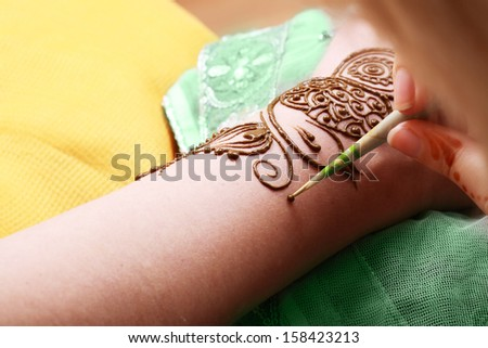 Image detail of henna being applied to hand over green fabric