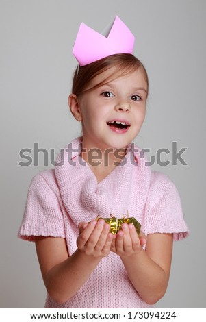 Image emotional joyful young girl with a beautiful smile in a knitted dress with a crown holding a gift on a gray background on Holiday/Little girl princess