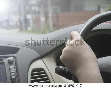Image filters tone light and effect, of a woman driving with hand on steering wheel on the road with selective focused point