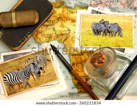 Image from a pile of old images on a desk and vintage objects with blurred background. The images on top are taken during a safari at the serengeti N.P. showing zebras  - stock photo