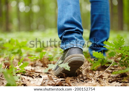 Image from the back of a man's feet walking through a forest on a footpath - stock photo