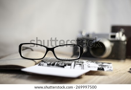 Image in retro style, old-fashioned camera and stylish glasses
