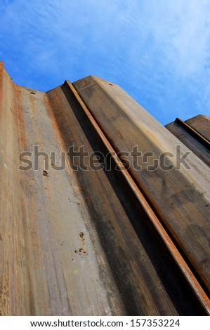 Image looking up some earth supporting sheet piles from down in an excavation on a construction site - stock photo