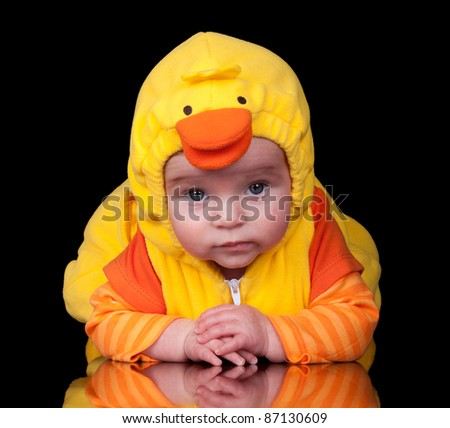 Image of a baby in a duck costume, isolated on black.