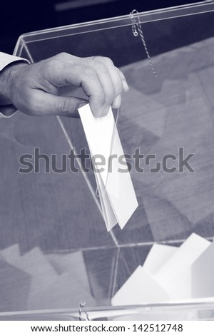 Image of a ballot box and hand putting a blank ballot inside,elections, voting concept - stock photo