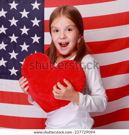 Image of a beautiful cheerful little girl with a sweet smile, holding a big red heart on the background of the American flag on Holiday - stock photo