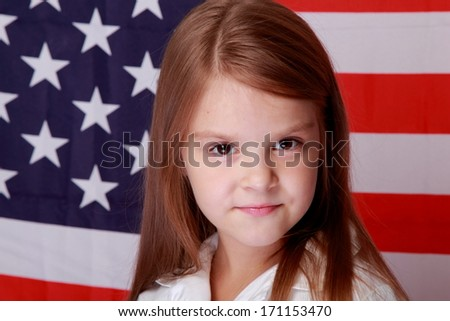 Image of a beautiful smiling little girl standing against the background of the American flag