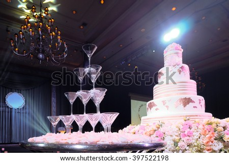 Image of a beautiful wedding cake and wine glasses on stage, with colourful spotlight, toned photo - stock photo
