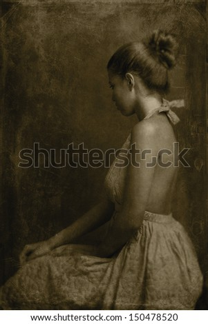 Image of a beautiful woman sitting. Monochrome image with sepia toning, texture, strong grain to create a retro looking photograph. Shallow depth of field.  - stock photo
