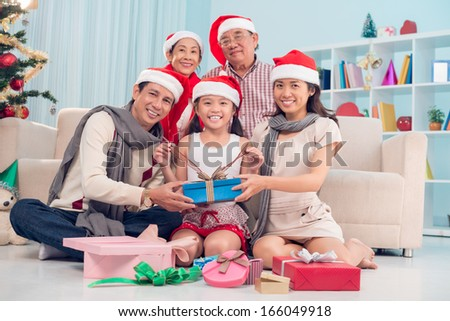 Image of a big family in Santa hat with Christmas presents sitting on the floor and looking at camera - stock photo