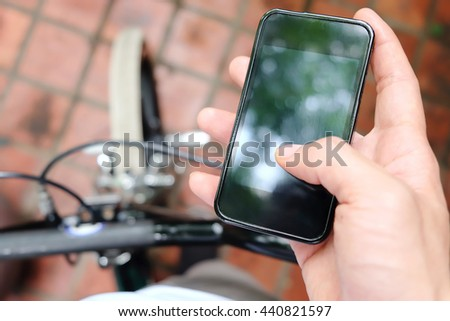 image of a biker texting on a smart phone