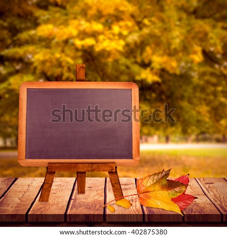 Image of a blackboard against large tree on meadow in the park - stock photo