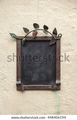 Image of a blackboard on wall with metal frame.  - stock photo