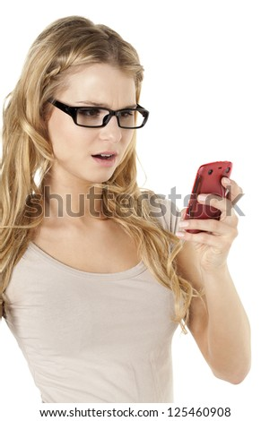 Image of a blond woman reading a text message on cellphone while standing against white background - stock photo