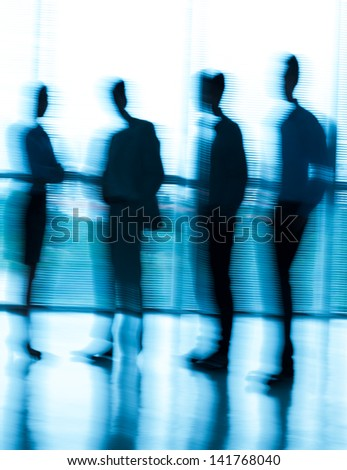 Image of a blurred business team standing at the office - stock photo