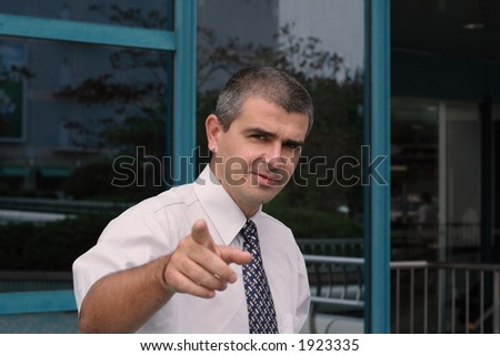 Image of a business leader giving working indications to his team in a city. Selective focus on the man, the background and the hand are blurred.