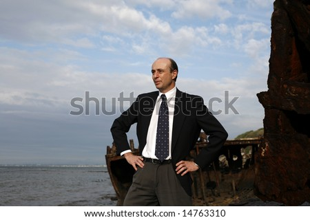Image of a business man in a strong pose on the wreck of a ship.
