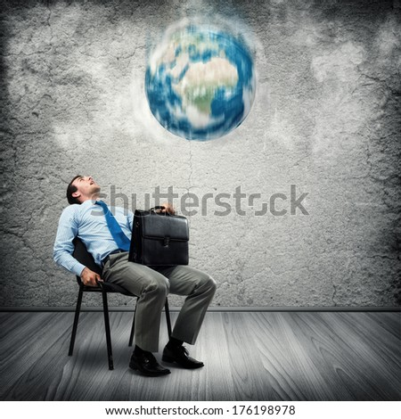 image of a business man looking at the falling planet. Elements of this image furnished by NASA - stock photo