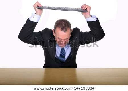 Image of a businessman at a desk about to smash a keyboard in frustration