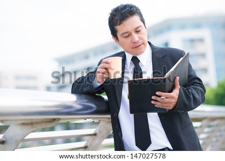 Image of a businessman concentrated on his notes outside