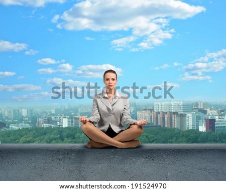 image of a businesswoman meditating on a concrete parapet - stock photo