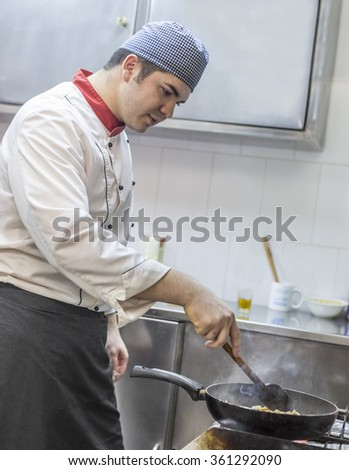 Image of a chef cooking pasta in a restaurant kitchen. - stock photo