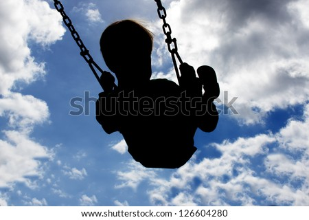 image of a child swinging, silhouetted against a blue sky with white clouds - stock photo