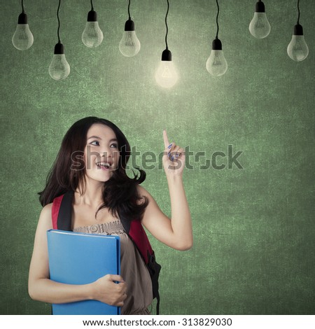 Image of a clever high school student getting idea and choose the bright light bulb in the classroom - stock photo