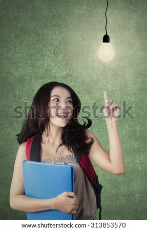 Image of a clever high school student standing in the classroom while pointing at a bright light bulb