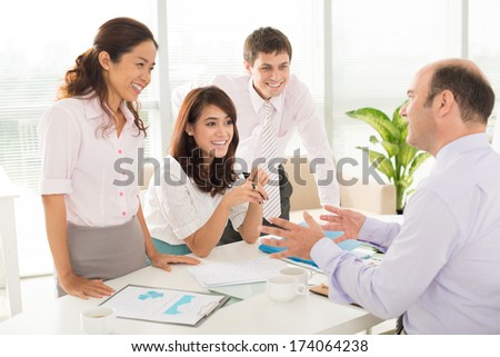 Image of a company staff consulting with her boss about some working moments at the office on the foreground  - stock photo