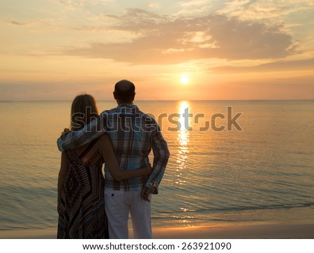 Image of a couple on the beach at sunset - stock photo
