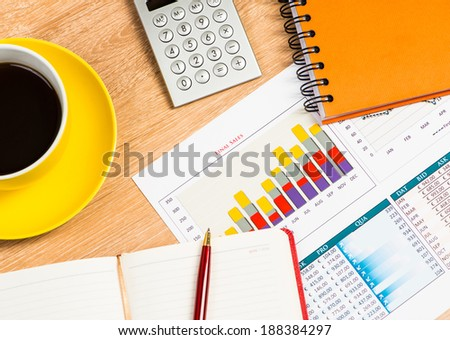 image of a cup of coffee, calculator, notepad and pen. business still life