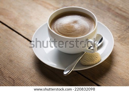 Image of a cup of coffee with an old vintage spoon and a vanilla cookie, placed on a wooden table top - stock photo