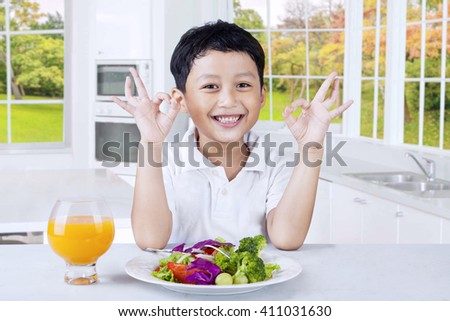 Image of a cute little boy with fresh vegetable salad in the kitchen showing OK sign