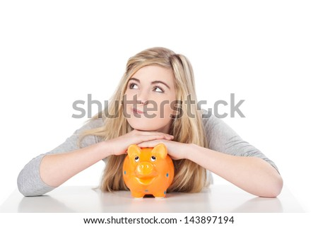 Image of a cute teenage girl posing with piggy bank. - stock photo