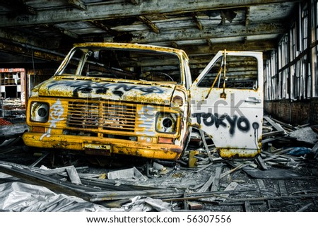 Image of a destroyed old, rusty truck covered in graffiti in an abandoned factory warehouse.