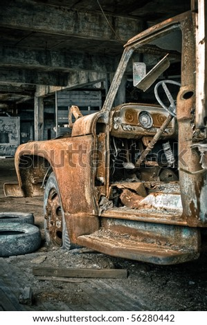 Image of a destroyed old, rusty truck in an abandoned factory warehouse.