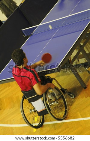 Image of a disabled man in wheelchair playing table tennis. Live image from an international tennis table competition for persons with disabilities. - stock photo