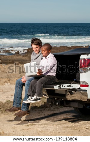 image of a dwarfish african man showing an young caucasian man something on the laptop while sitting on the back of a pickup truck