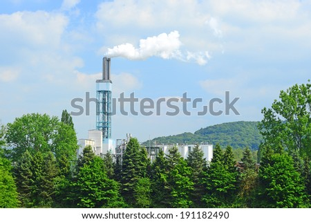 Image of a factory pumping fumes high into the sky - stock photo